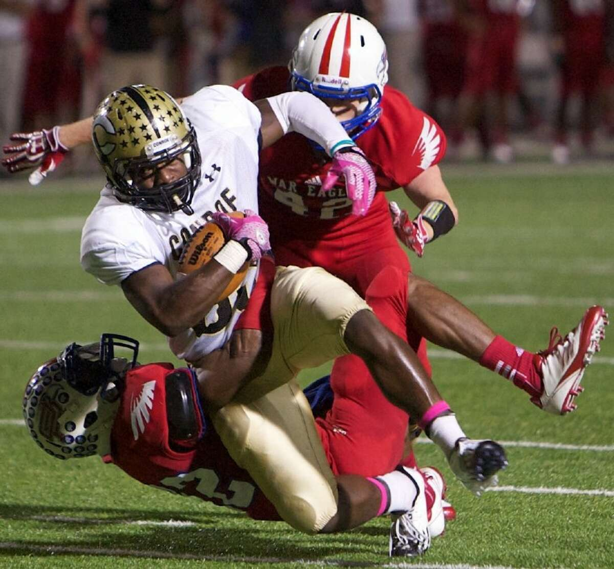 Conroe's Larry Day battles against a pair of Oak Ridge defenders during Friday night's district game at Woodforest Bank Stadium in Shenandoah. To view or purchase this photo and others like it visit: www.yourconroenews.com/photos