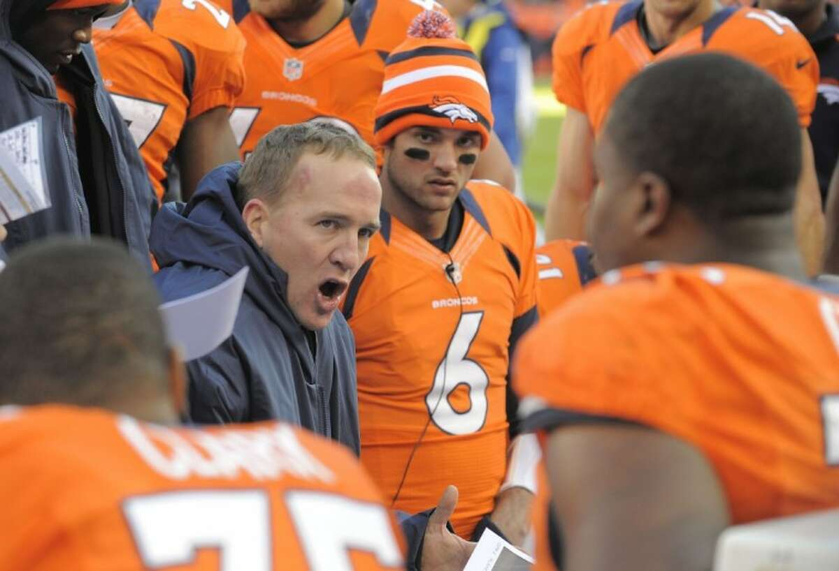 Denver Broncos quarterback Peyton Manning talks to teammates on the bench during Sunday's game against the Cleveland Browns in Denver. The Broncos won, 34-12.