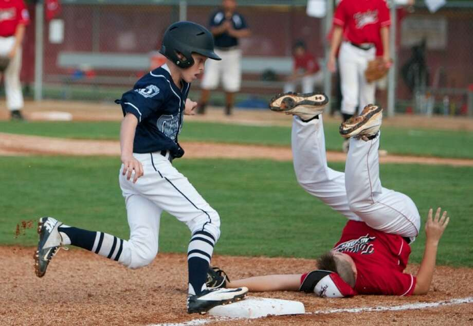 ORWALL National's Cooper Lucas rounds third base as Tomball's Cameron Hunter takes a tumble during Saturday's Little League Texas East District 28 Majors tournament championship game at the ORWALL Complex in Spring. Photo: Staff Photo By Eric Swist