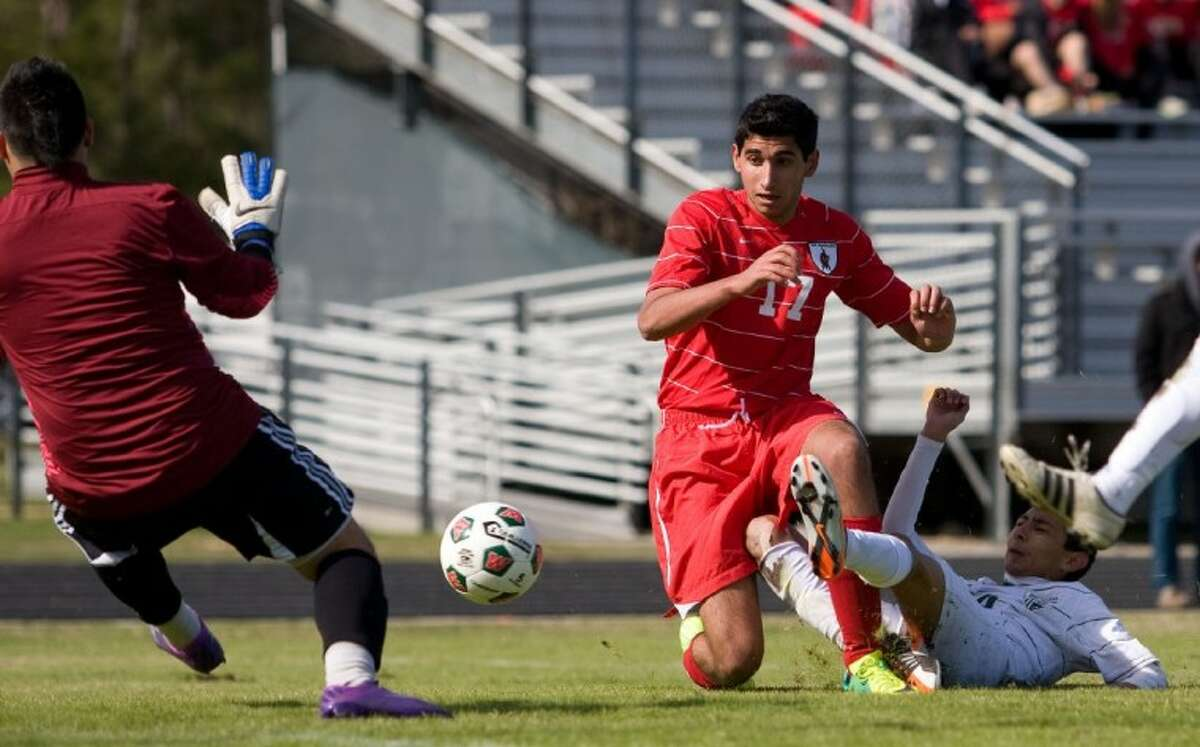 Spring defender Melvin Lemus deflects The Woodlands senior forward Wassim Ghanem's shot, which was stopped by goalkeeper Josue Maldanado, during the first half of the teams' game Thursday at the Kilt Cup at The Woodlands High School.