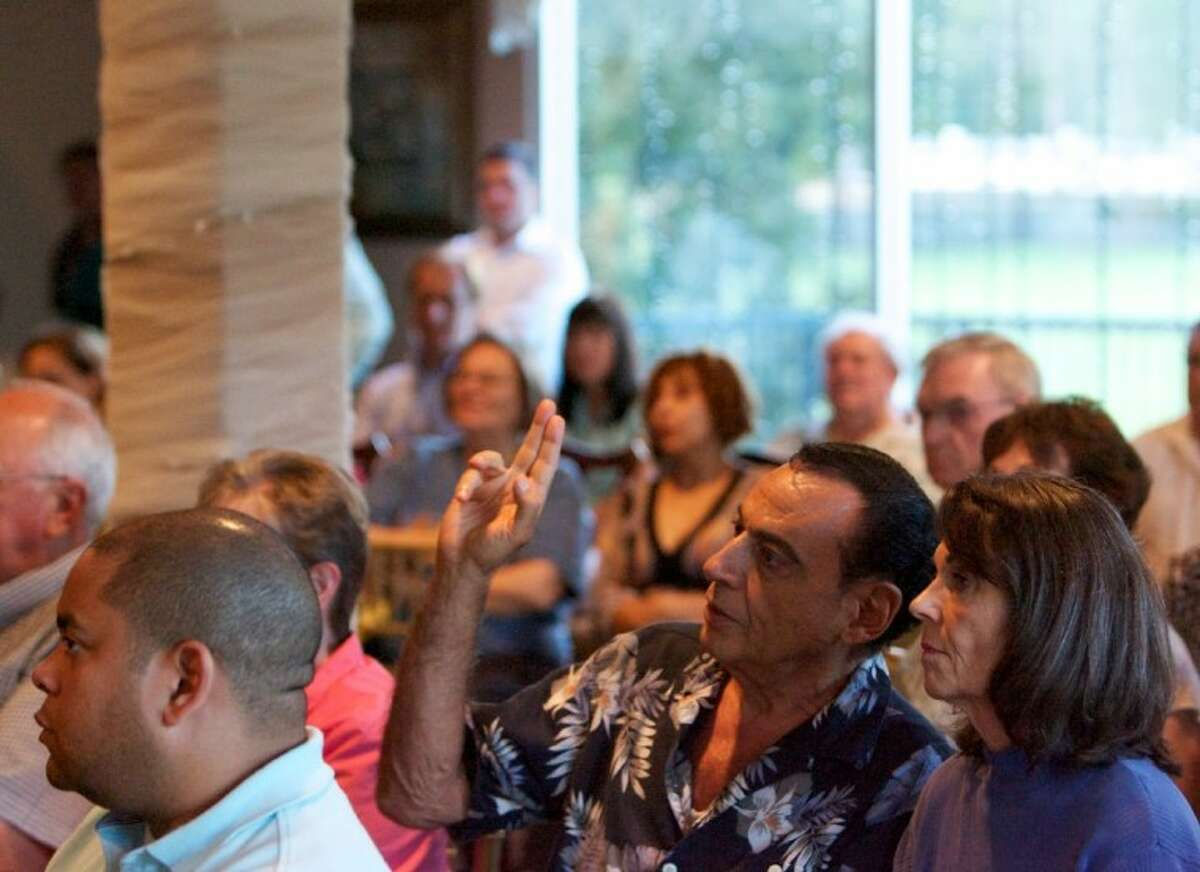 A resident raises his hand with a question for Texas Railroad Commissioner candidate Greg Parker. Montgomery County residents gathered Tuesday at the River Plantation Country Club for a Citizens Residents Oppose Wells meeting where Parker was a speaker.