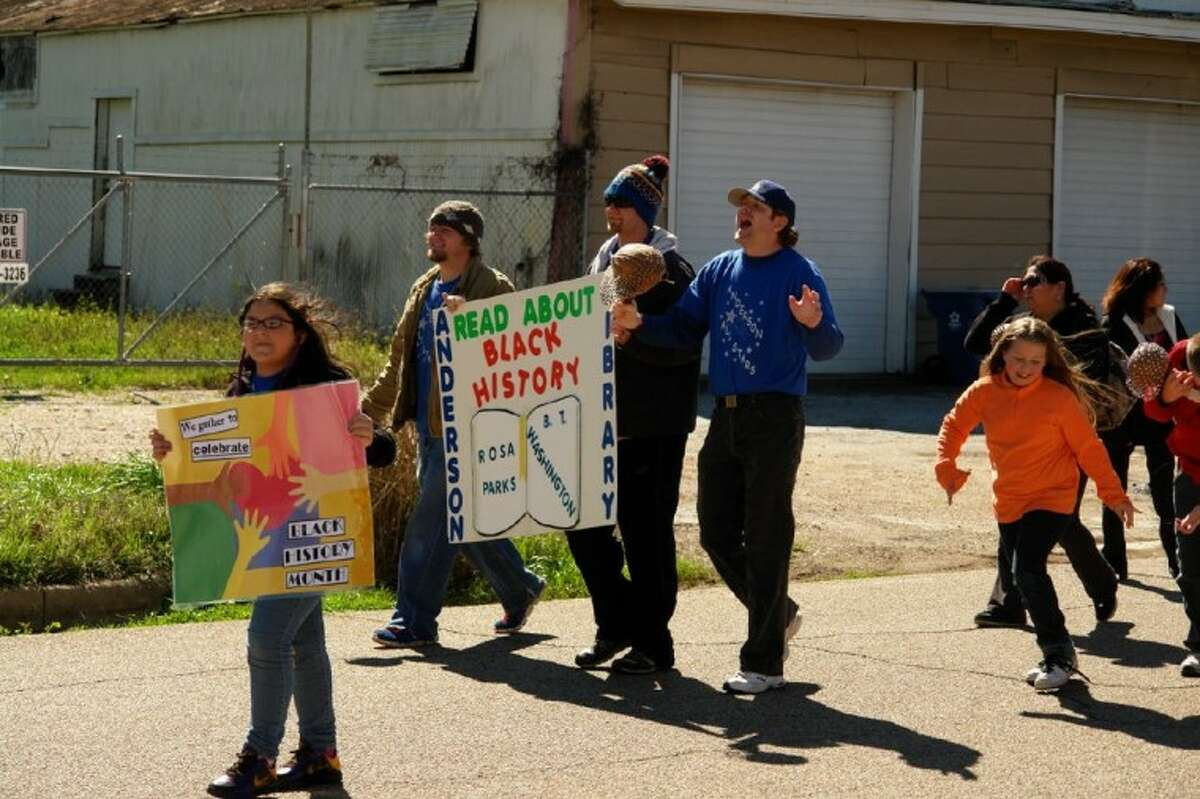 Members and supporters with Anderson Elementary School raise signs in honor of equality and Black History Month education Saturday in the Project Hope Black History Parade in Conroe.