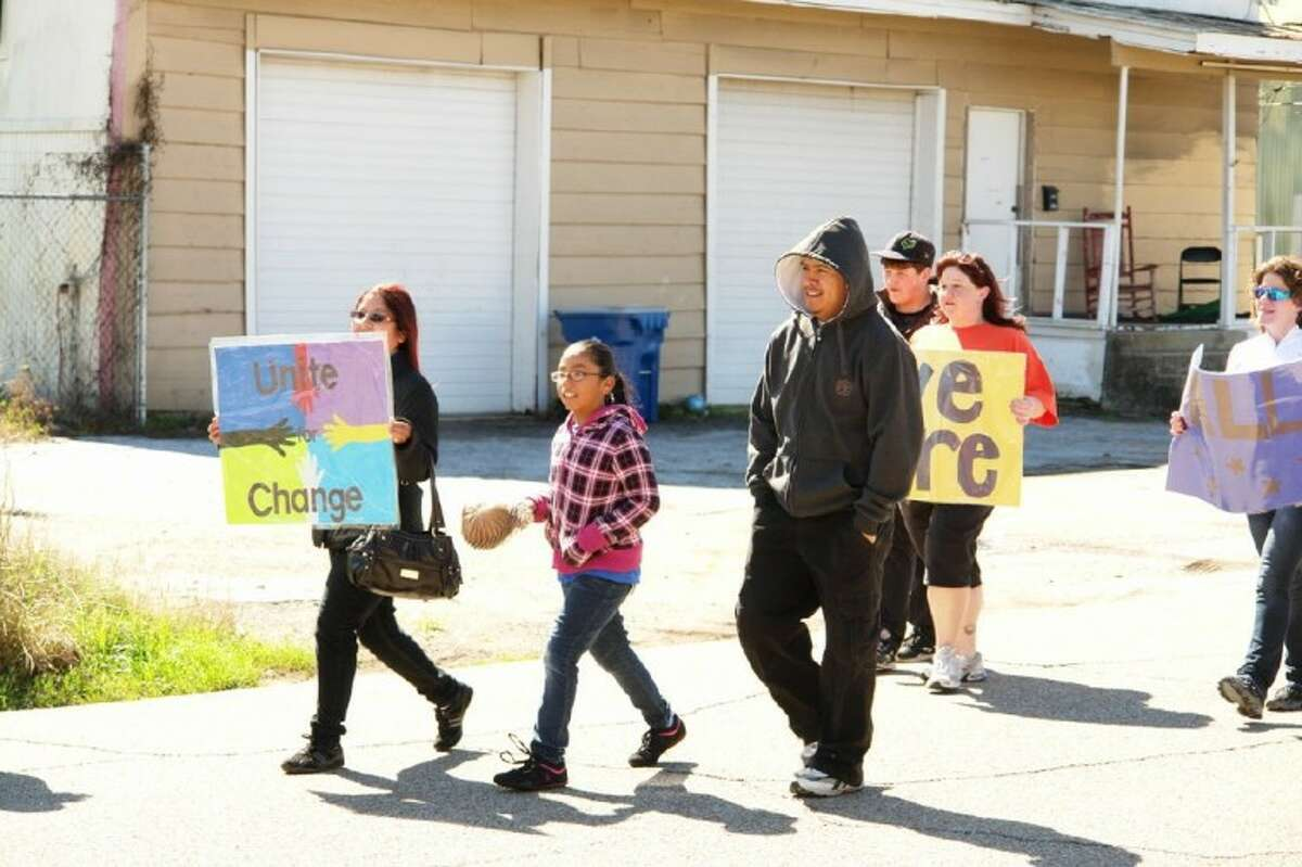 """Participants in Saturday's Project Hope Parade in Conroe hold signs advocating to """"Unite for Change"""" and reminding the community that everyone is equal."""