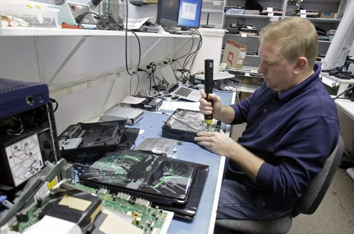 Technician Shawn Cable repairs a video game console at the Laptops Plus computer store in Winter Park, Fla., Thursday, Jan. 5, 2012. A burst of hiring in December pushed the unemployment rate to its lowest level in nearly three years, giving the economy a boost at the end of 2011.