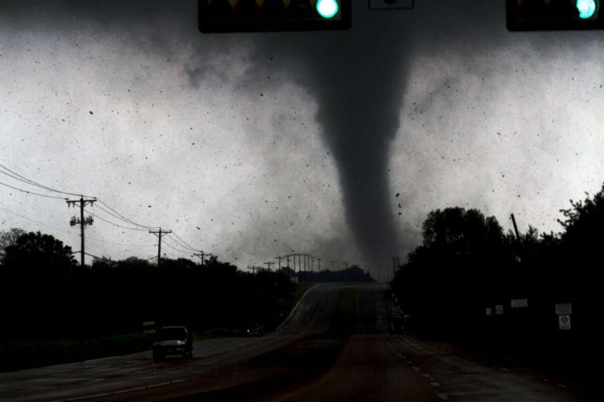 A tornado touches down in Lancaster, south of Dallas, on Tuesday. Tornadoes tore through the Dallas area Tuesday, peeling roofs off homes, tossing big-rig trucks into the air and leaving flattened tractor trailers strewn along highways and parking lots.