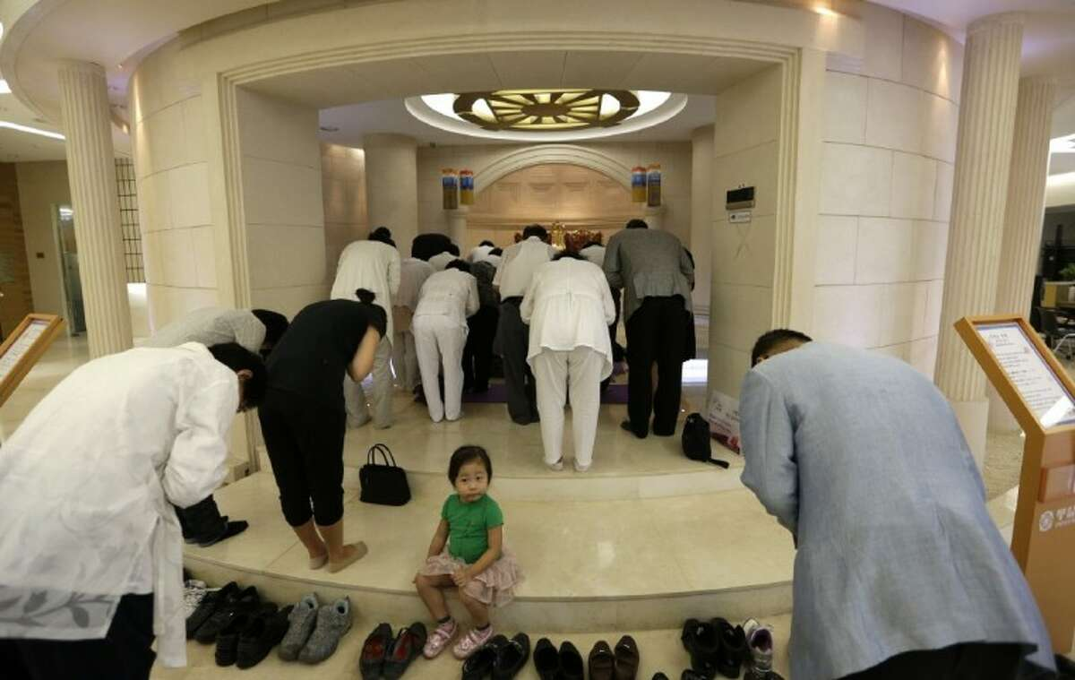 A girl sits as followers pray for the Rev. Sun Myung Moon during a service at a Unification church in Seoul, South Korea Monday. Moon, the self-proclaimed messiah who founded the church, died Monday, at a church-owned hospital near his home in Gapyeong County, northeast of Seoul, church officials said. He was 92.