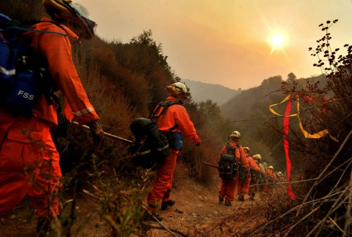 A female inmate fire crew hikes up to the fire line as they continue working on the Williams Fire that has scorched over 4,000 acres near Glendora, Calif. Monday.