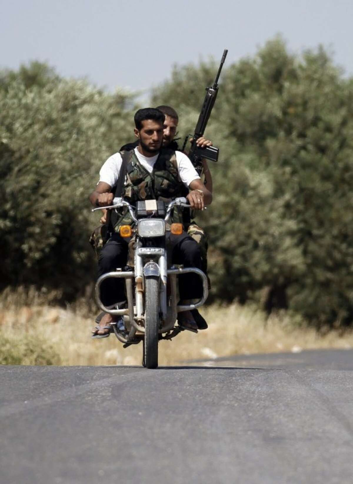 Armed Free Syrian Army soldiers ride a motorcycle on the outskirts of Idlib, Syria, Sunday. Free Syrian Army soldiers are determined to bring down the regime by force of arms, targeting military checkpoints and other government sites. A U.N. observer team with nearly 300 members has done little to quell the bloodshed.