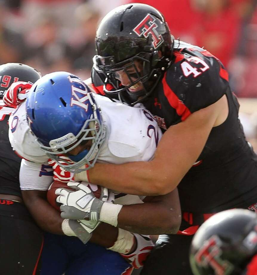 Texas Tech's Jackson Richards tackles Kansas running back James Sims. The Red Raiders won 41-34 in two overtimes. Photo: Zach Long