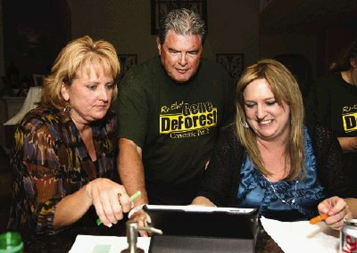 Gene DeForest looks over early election returns at a watch party in his home Tuesday night with Marie Moore-Hermansen, left, and Anita Geiser.