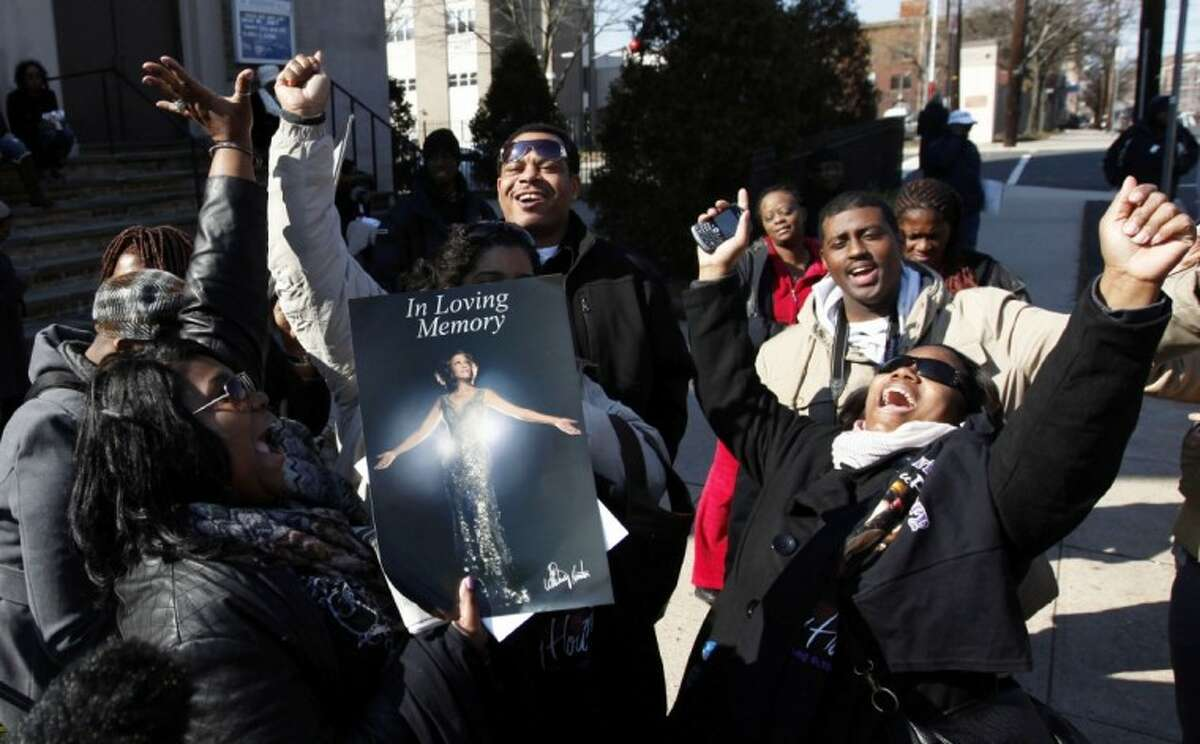 Fans sing Whitney Houston songs as they gather a few blocks from the New Hope Baptist Church before the singer's funeral in Newark, N.J., Saturday.