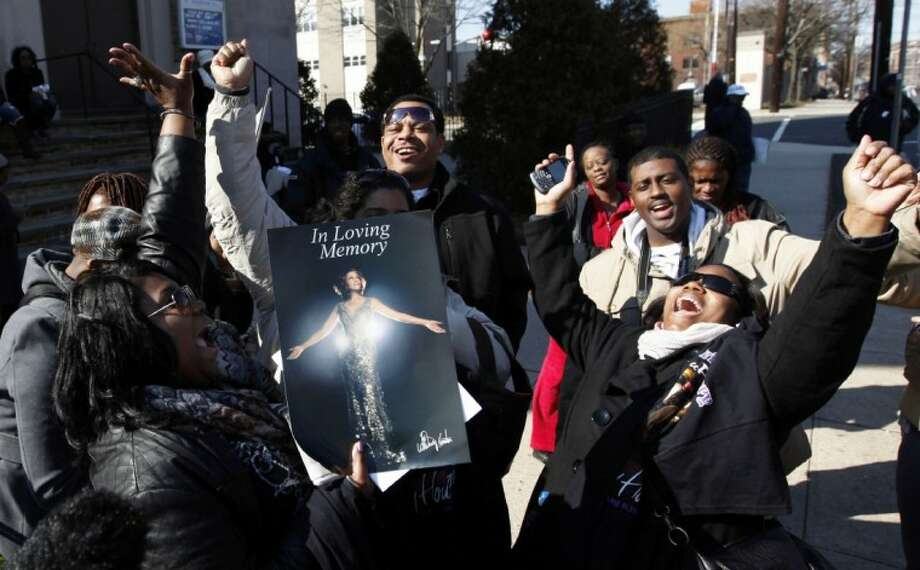 Fans sing Whitney Houston songs as they gather a few blocks from the New Hope Baptist Church before the singer's funeral in Newark, N.J., Saturday. Photo: Jason DeCrow