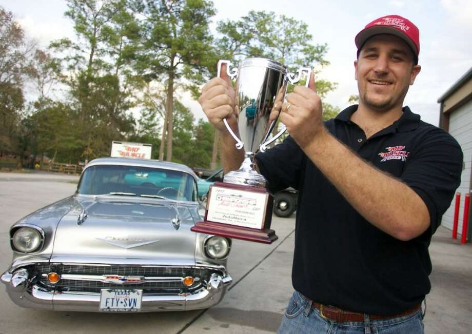 Blake Meaux holds a 2012 Houston Autorama championship trophy won by Rob Bryngelson's 1957 Chevy rebuilt by his shop, Mo' Muscle Cars.