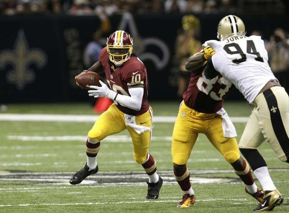 Redskins quarterback Robert Griffin III finds an opening against the Saints in New Orleans. Griffin and the Redskins won in an upset 40-32. Photo: Matthew Hinton