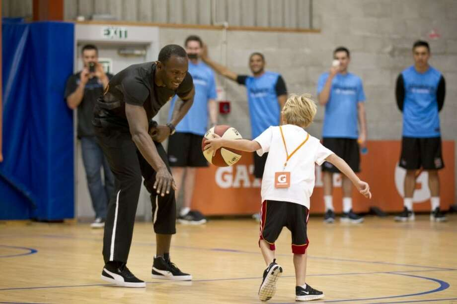 Olympic sprint champion Usain Bolt, here participating in a basketball clinic in New Zealand, plans to defend his 100- and 200-meter titles in 2016. Photo: Dean Purcell