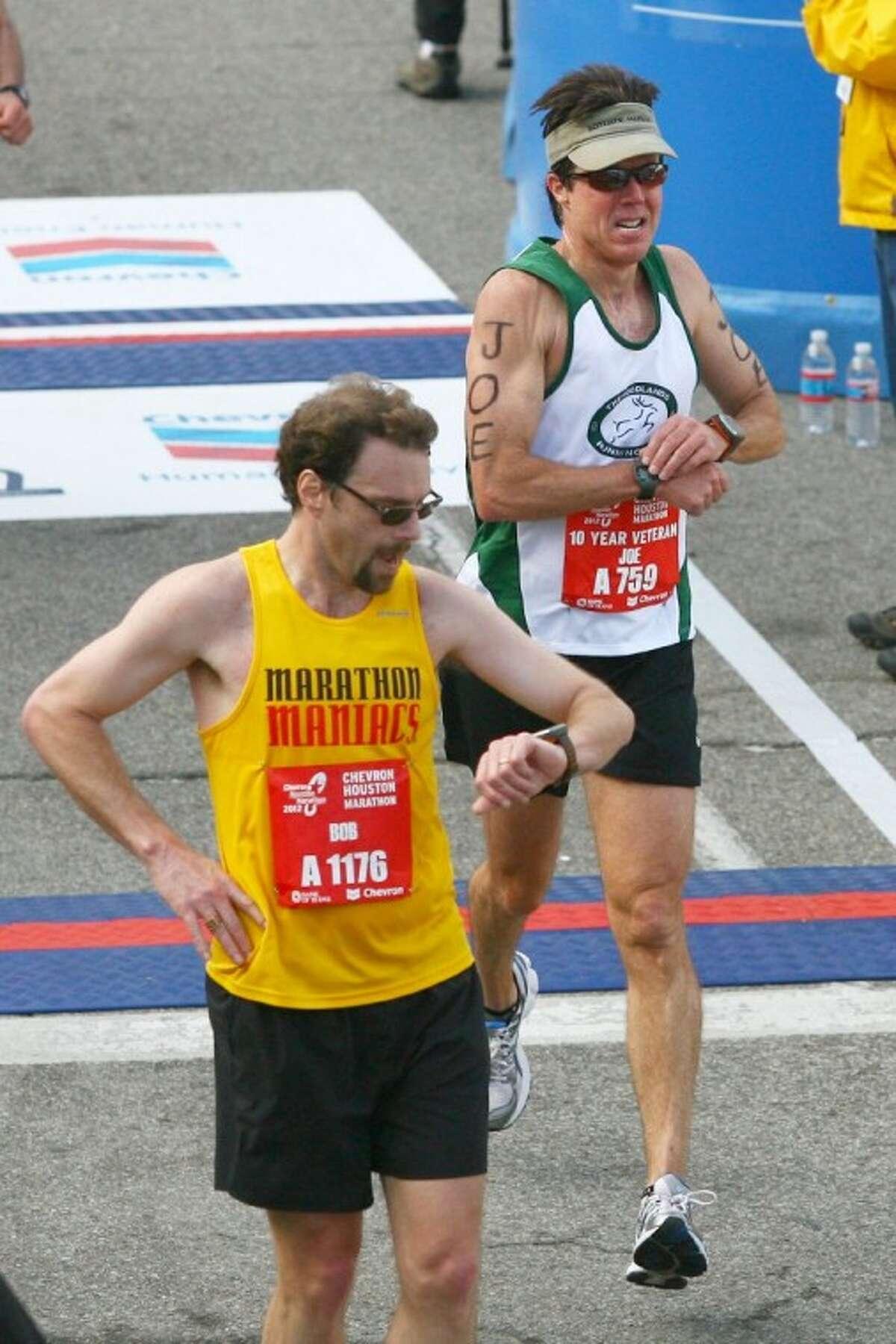 Joe Killeen, of The Woodlands, crosses the finish line Sunday at the Chevron Houston Marathon in Houston.