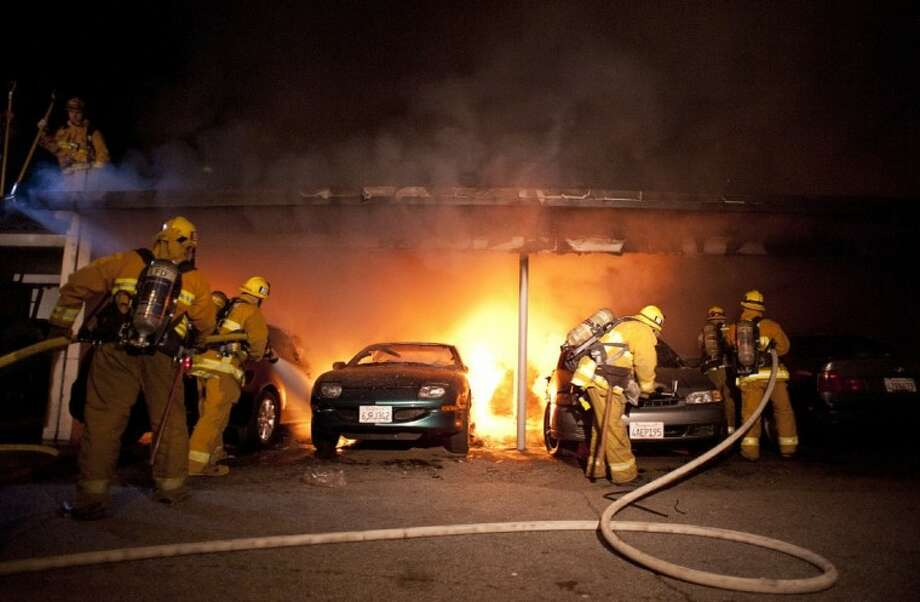 Los Angeles Fire Department firefighters extinguish numerous cars on fire in a carport in the Sherman Oaks neighborhood of Los Angeles on Monday. For the fifth night in a row, a spate of arson fires has sent firefighters scrambling to extinguish car fires in the Hollywood, Hollywood Hills, Studio City and Sherman Oaks neighborhoods of Los Angeles. Photo: DAN STEINBERG