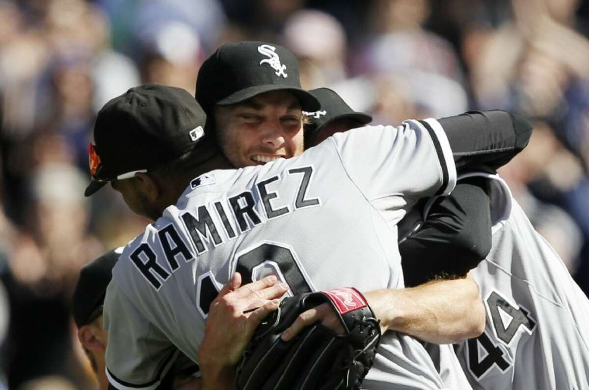 Chicago White Sox starting pitcher Phil Humber, center, is mobbed by teammates after pitching a perfect baseball game against the Seattle Mariners Saturday in Seattle. The White Sox won 4-0.