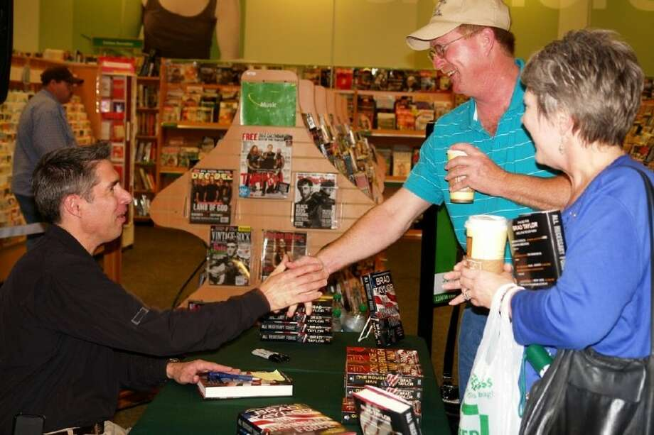"Brad Taylor, best-selling author and graduate of Conroe High, spoke to fans and signed books Sunday at Hastings in Conroe. His second novel, ""All Necessary Force,"" recently was released and follows the characters of his 2010 bestseller ""One Rough Man."" Photo: Staff Photo By Carrie Thornton"
