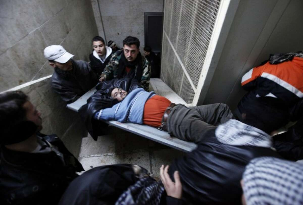 An injured Syrian rebel fighter is carried into a local hospital following an exchange of fire with army troops, unseen in Idlib, Syria, Wednesday. The European Union will impose harsher sanctions on Syria, a senior EU official said Wednesday, as Russia tried to broker talks between the vice president and the opposition to calm violence. Activists reported at least 50 killed in the regime's siege of the restive city of Homs.