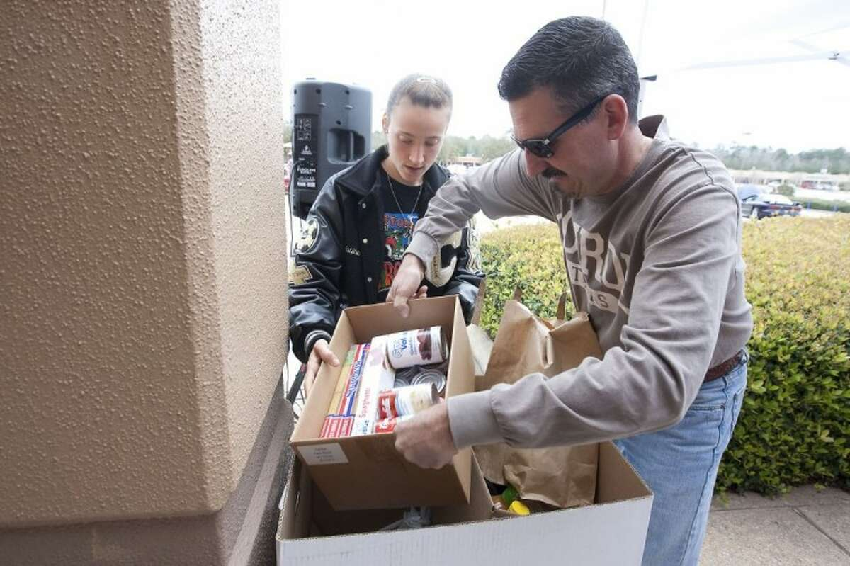 Robert and Kristina Wear make a food donation during the Crusin' Against Hunger Food Drive on Saturday at the Outlets of Conroe.