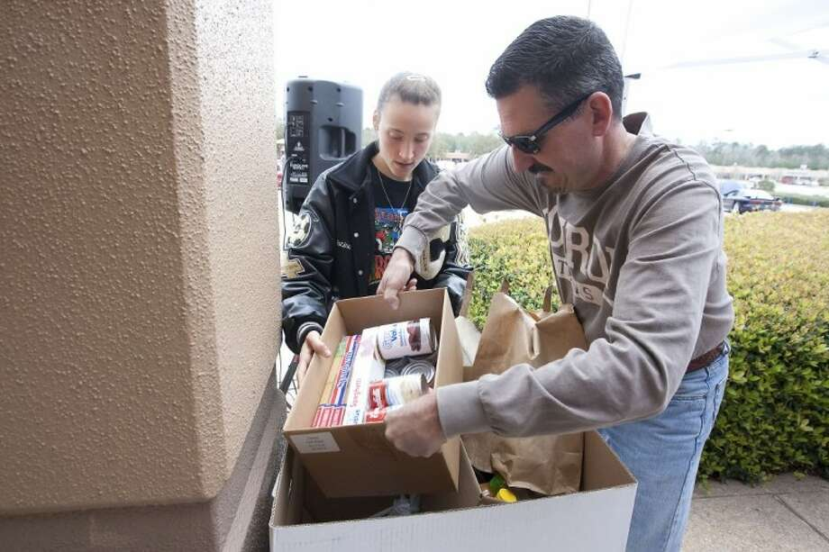 Robert and Kristina Wear make a food donation during the Crusin' Against Hunger Food Drive on Saturday at the Outlets of Conroe. Photo: Karl Anderson