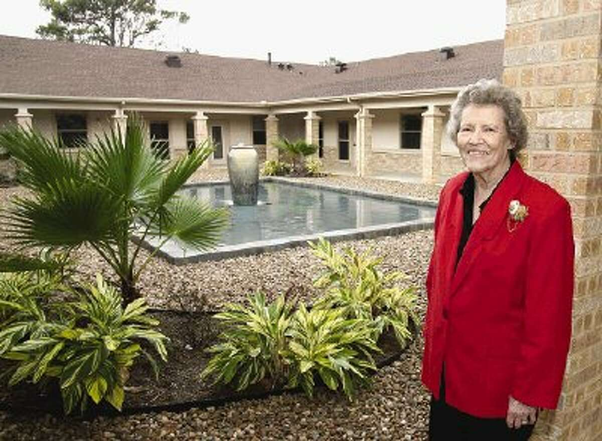 Hazel Smith, 87, the first official resident of Live Oak Assisted Living, admires the reflection pool in the facility's center courtyard.