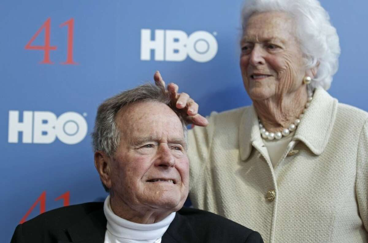 """Former first lady Barbara Bush touches the hair of her husband President George H.W. Bush as they arrive for the premiere of HBO's new documentary on his life in Kennebunkport, Maine, Tuesday. The premiere of """"41"""" was held Tuesday on Bush's 88th birthday on the grounds of St. Ann's Church in Kennebunkport, near the Bush family's summer home."""