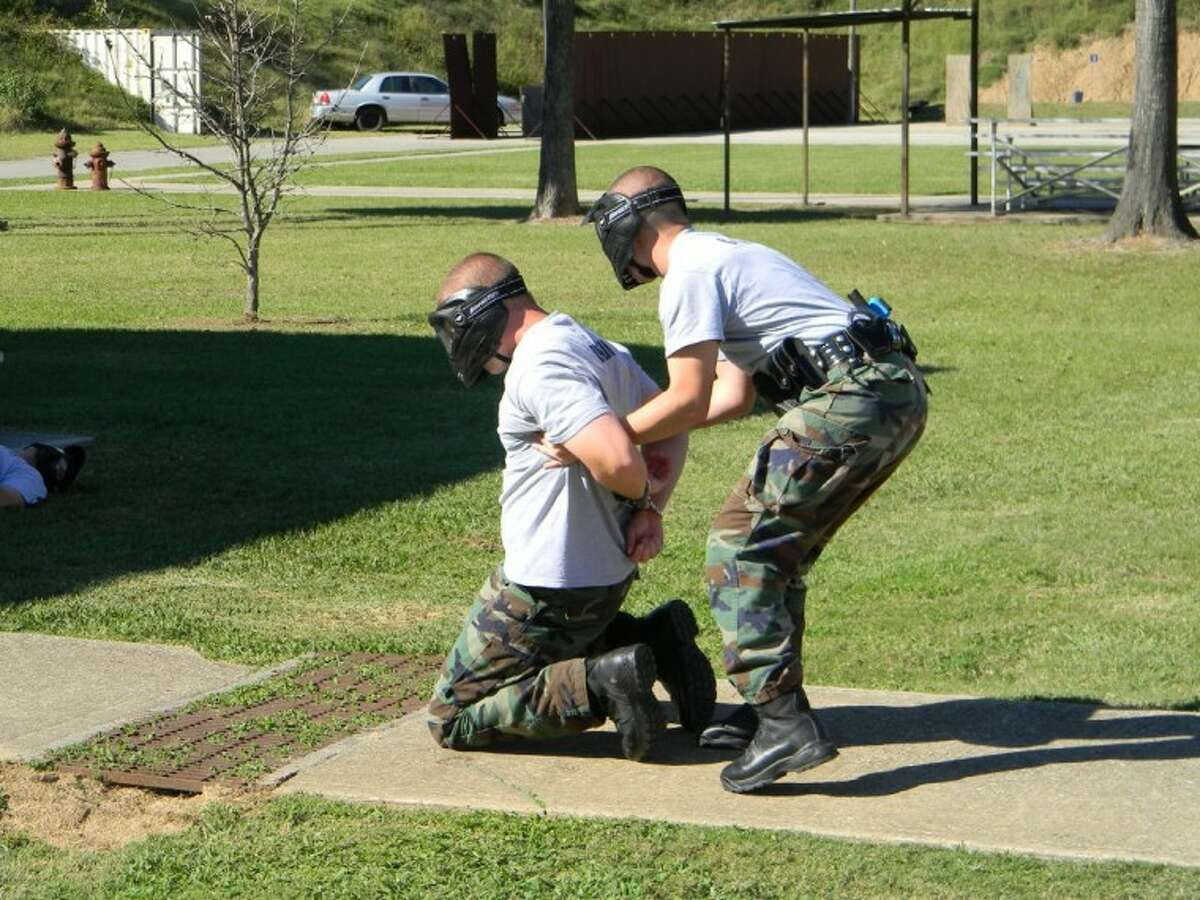 An officer in training cuffs another fellow student at the FBI Firearms Facility in Conroe during a training scenario as part of the Conroe Police Department's academy. Ten officers will be graduating from the department's third academy tonight.