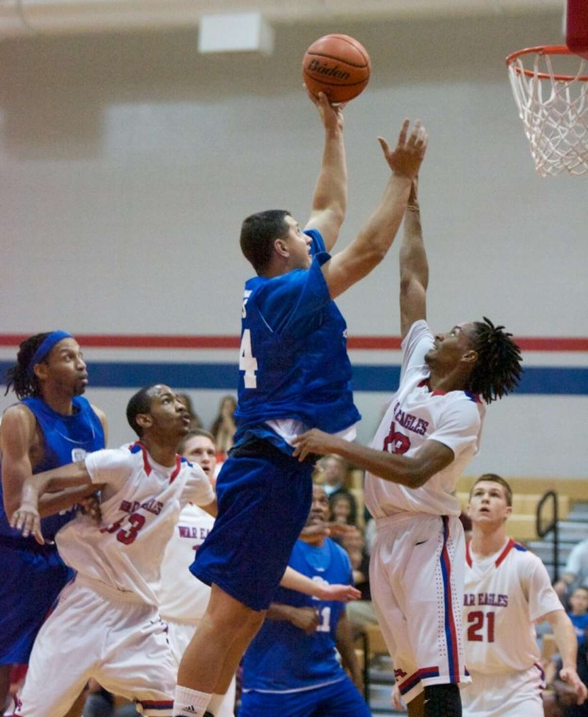Alum Clint Laskoskie battles against Oak Ridge's Trumaine Jefferson as he goes up for a basket during Friday night's game at Oak Ridge High School. Oak Ridge High School varsity basketball team alumni from previous years returned to play against this years current varsity team.