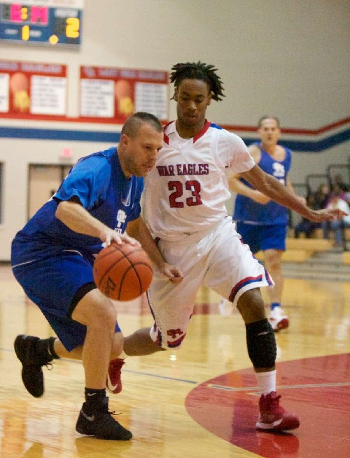 Alum Todd Lembrich dribbles against Oak Ridge's Trumaine Jefferson during Friday night's game at Oak Ridge High School. Oak Ridge High School varsity basketball team alumni from previous years returned to play against this years current varsity team.