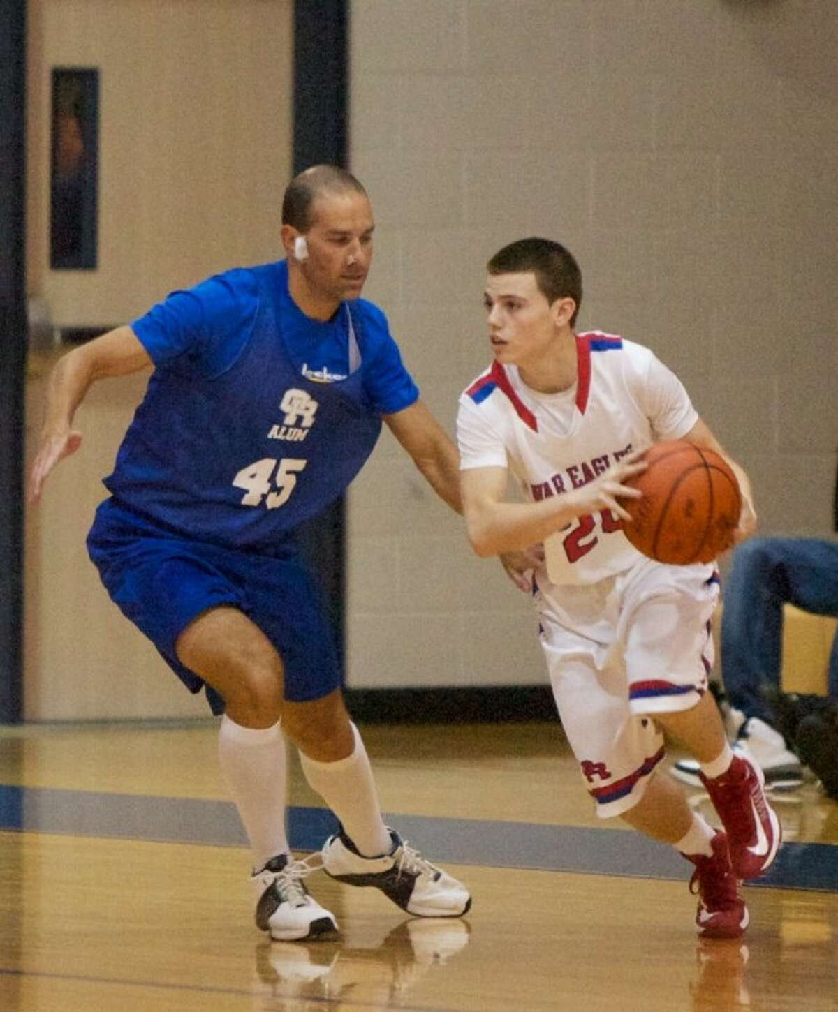 Oak Ridge's Robbie Bull maneuvers past Alum Casey Clark during Friday night's game at Oak Ridge High School. Oak Ridge High School varsity basketball team alumni from previous years returned to play against this years current varsity team.