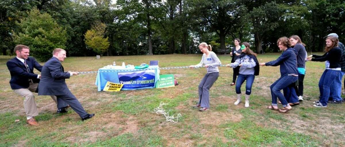 """Local groups from Pittsburgh take part in a Frackdown Smackdown tug-of-war between college students representing the """"gas industry"""" and Pennsylvania citizens during a global Frackdown Day Schenley Park in Pittsburgh Saturday."""