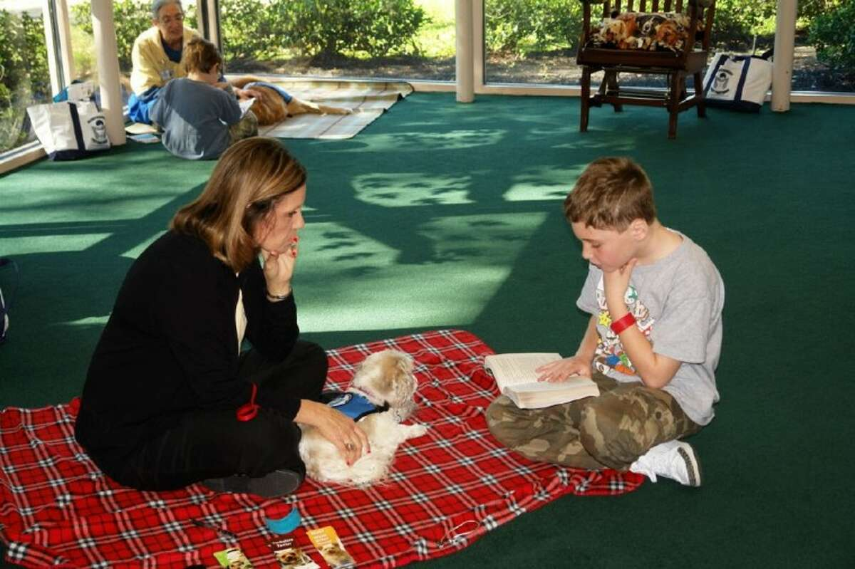 Sean Atun, 9, reads to a Montgomery Pet Partners volunteer and dog Saturday at the Reading with the Dogs program at the South Regional Library in The Woodlands.