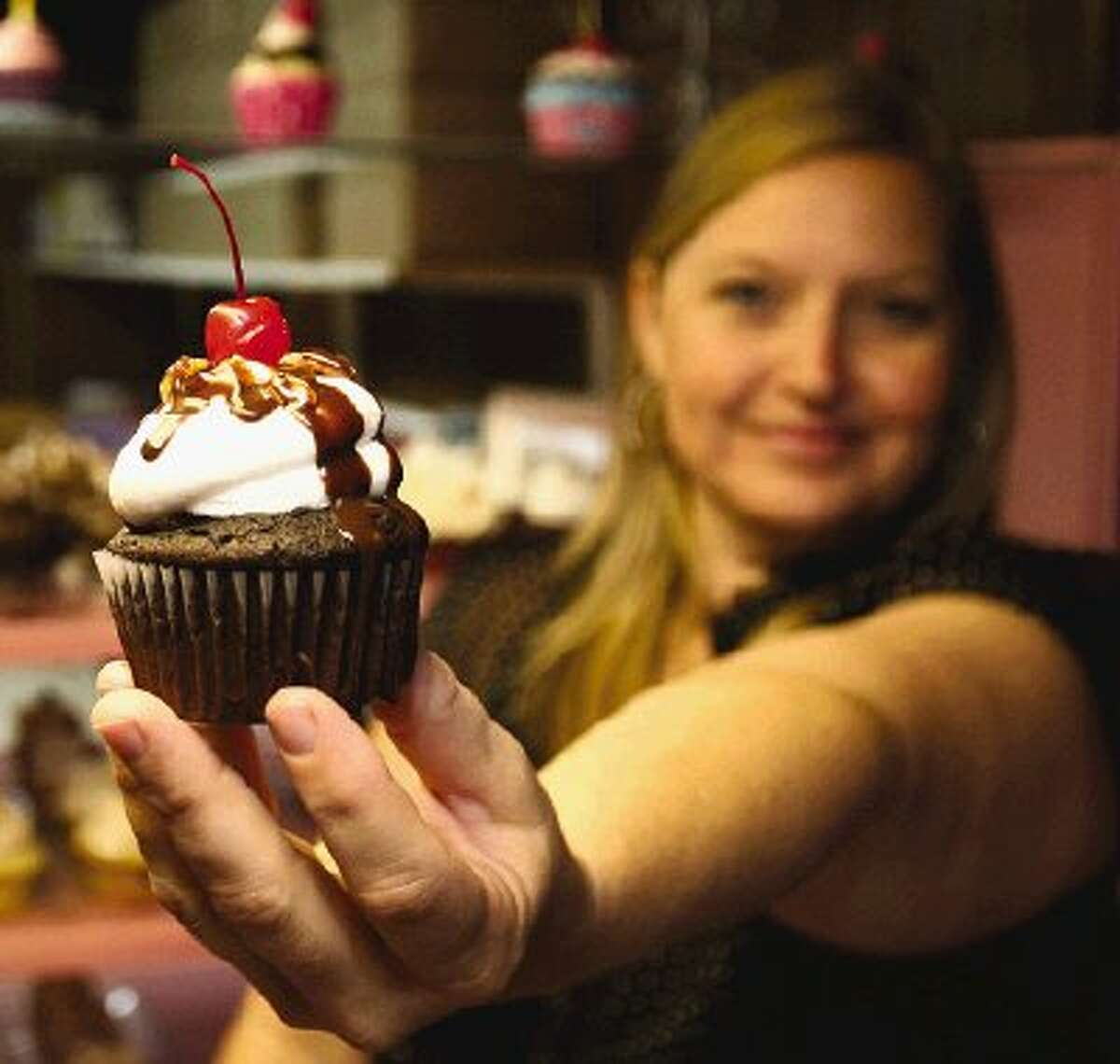 Candyland Sweets owner Ami Fairchild shows off one of the 80 different varieties of specialty cupcakes she makes for customers.