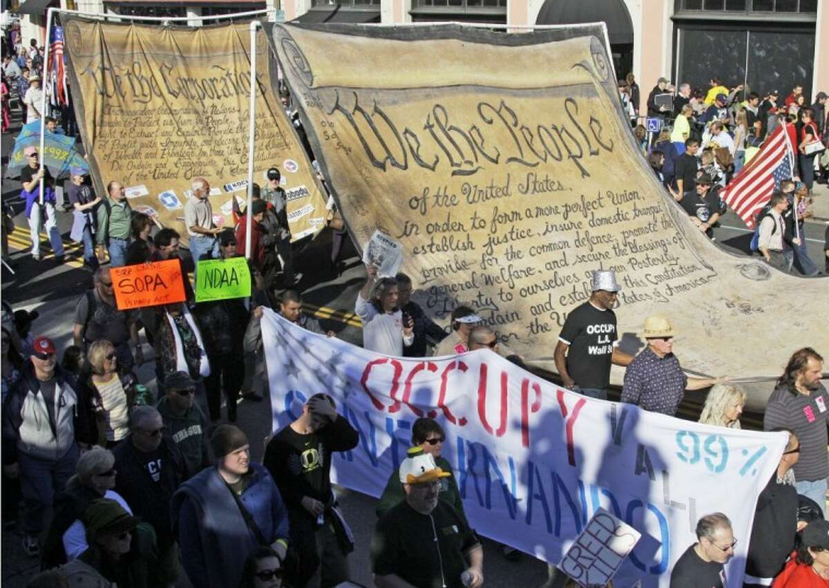 """Occupy the Rose Parade protesters carry an oversize copy of the preamble to the U.S. Constitution, followed by a """"corporate"""" version of the document, as they march in a prearranged demonstration at the end of the 123rd Rose Parade in Pasadena, Calif. Monday."""