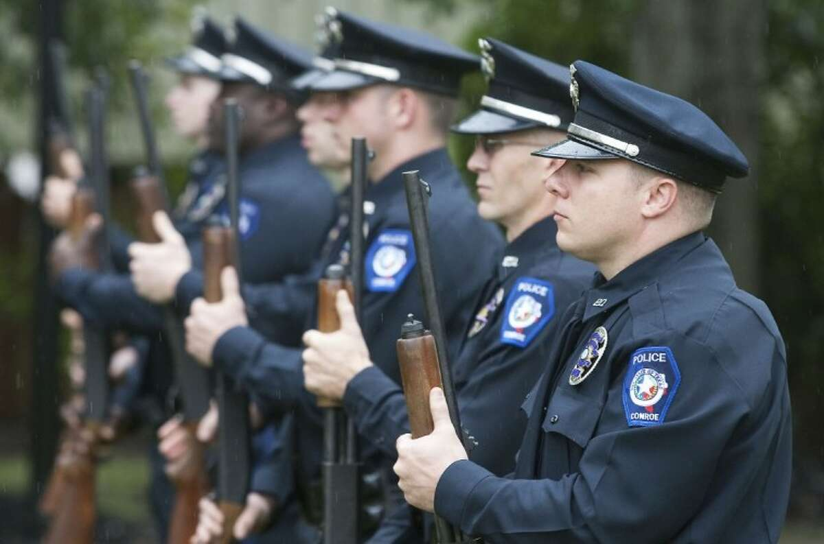 Conroe police officers perform a 21- gun salute during the Conroe Police Department's annual ceremony for Peace Officers Memorial Day Tuesday at Heritage Place Park in Conroe.