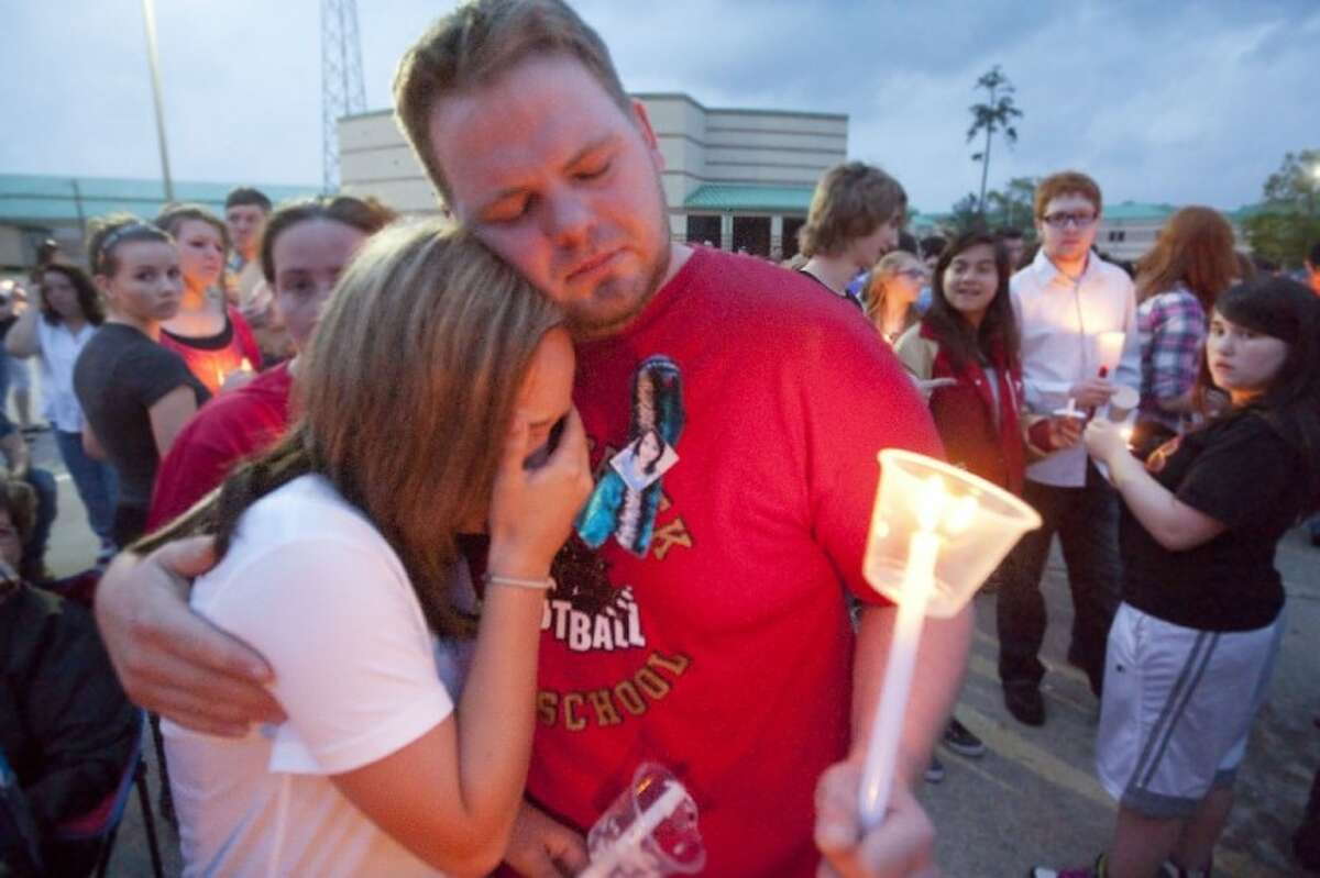 Kyle and Kim Irbin, Halie McDonald's aunt and uncle, embrace during a vigil Sunday at Caney Creek High School remembering the numerous students who have died since 2005.