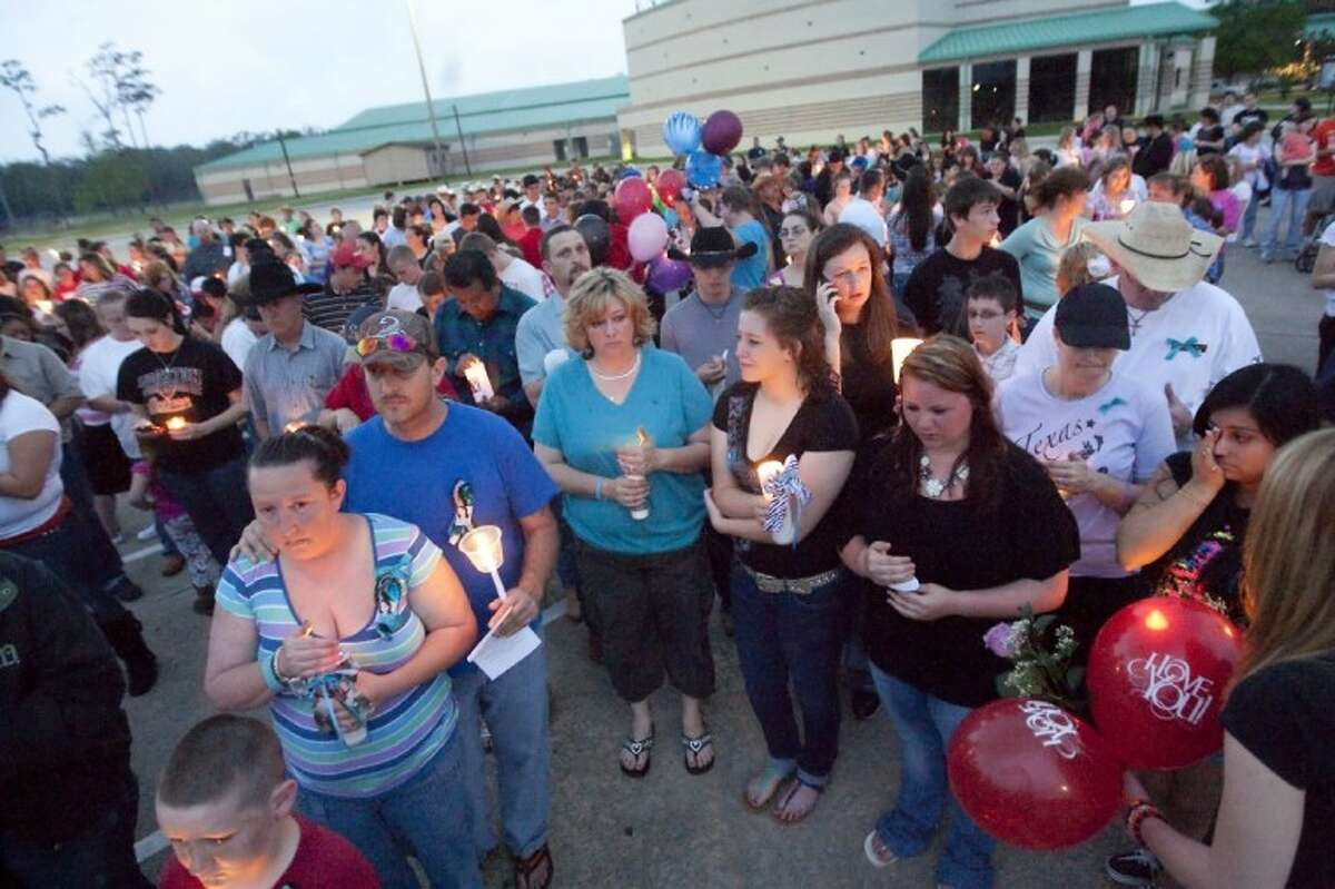 Students and community members attend a vigil Sunday at Caney Creek High School remembering the numerous students who have died since 2005.