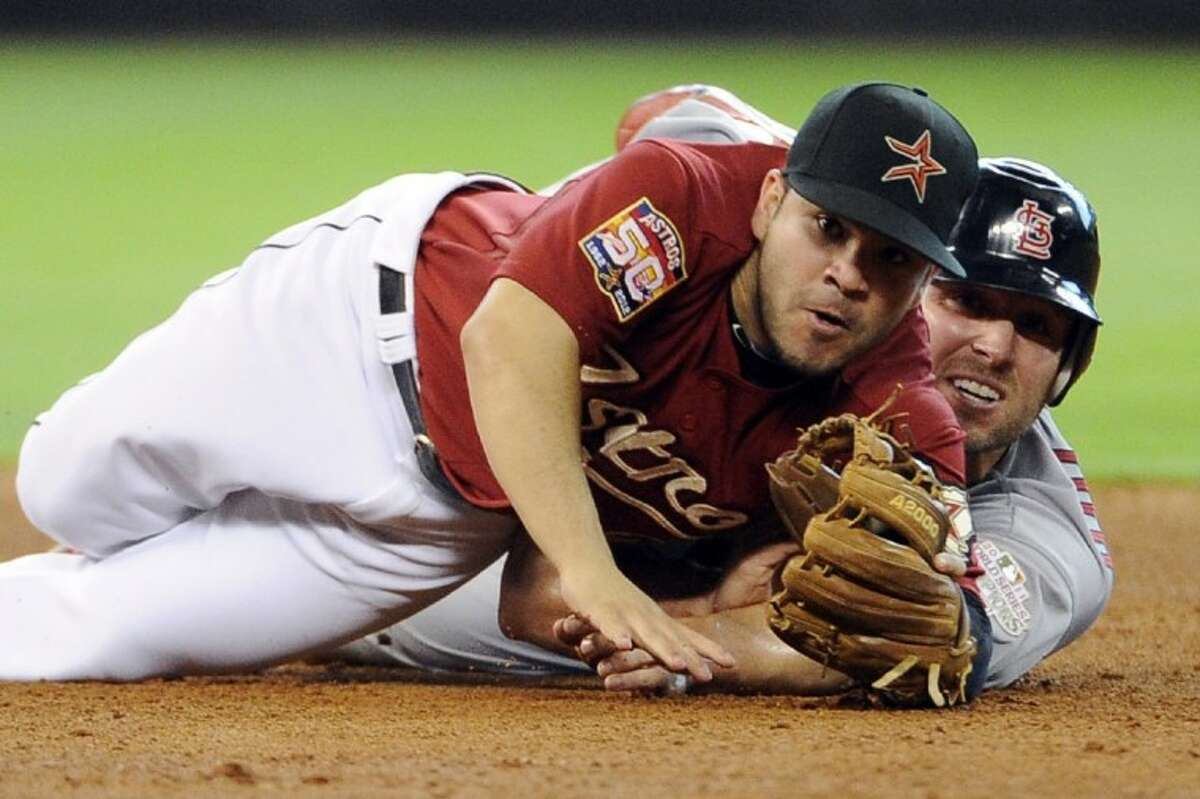 Houston Astros second baseman Jose Altuve, left, and St. Louis Cardinals' Matt Holliday, right, look to first base to see that Cardinals' Allen Craig was out on the double play in the fifth inning of a baseball game, Sunday in Houston.