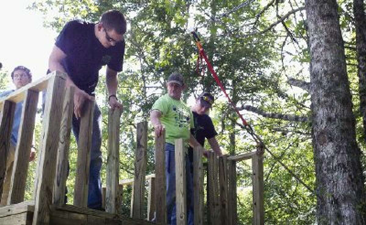 Calvary Baptist School students and volunteers build a zip line at Gospel Lakes Ranch in New Waverly Thursday as part of a community Serve-a-Thon event.