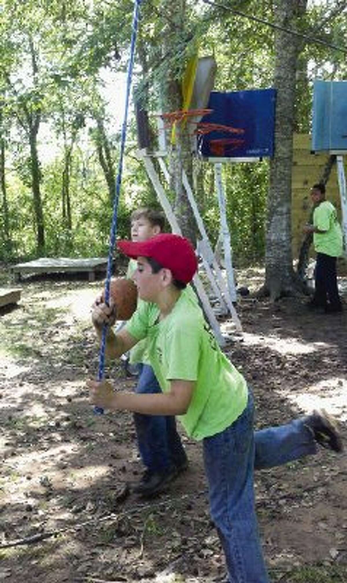 Calvary Baptist School students play around a challenge course while watching other students and volunteers build a zip line at Gospel Lakes Ranch in New Waverly Thursday.