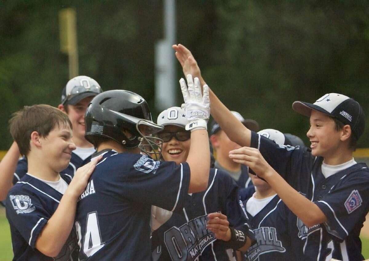 Teammates congratulate ORWALL National's Oscar Kanada at home plate after he hit a home run during Wednesday night's Texas East Little League Section 2 tournament game against Bridge City at the ORWALL Complex in Spring.