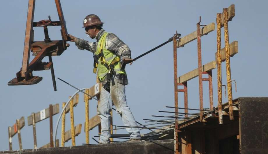 A construction worker directs a steel hoist at the foundation of a new condo complex in Sunrise, Fla., Thursday. A burst of hiring in December pushed the unemployment rate to its lowest level in nearly three years, giving the economy a boost at the end of 2011. Photo: J Pat Carter