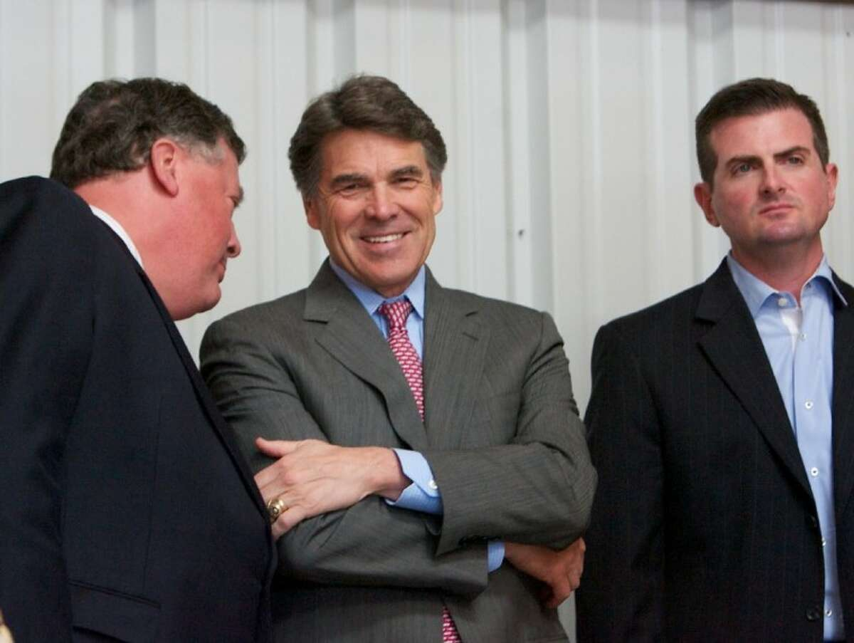 State Sen. Tommy Williams, R-The Woodlands, left, speaks with Texas Gov. Rick Perry, center, as he stands alongside state Rep. Brandon Creighton, R-Conroe, before addressing the media Wednesday in Cut and Shoot.