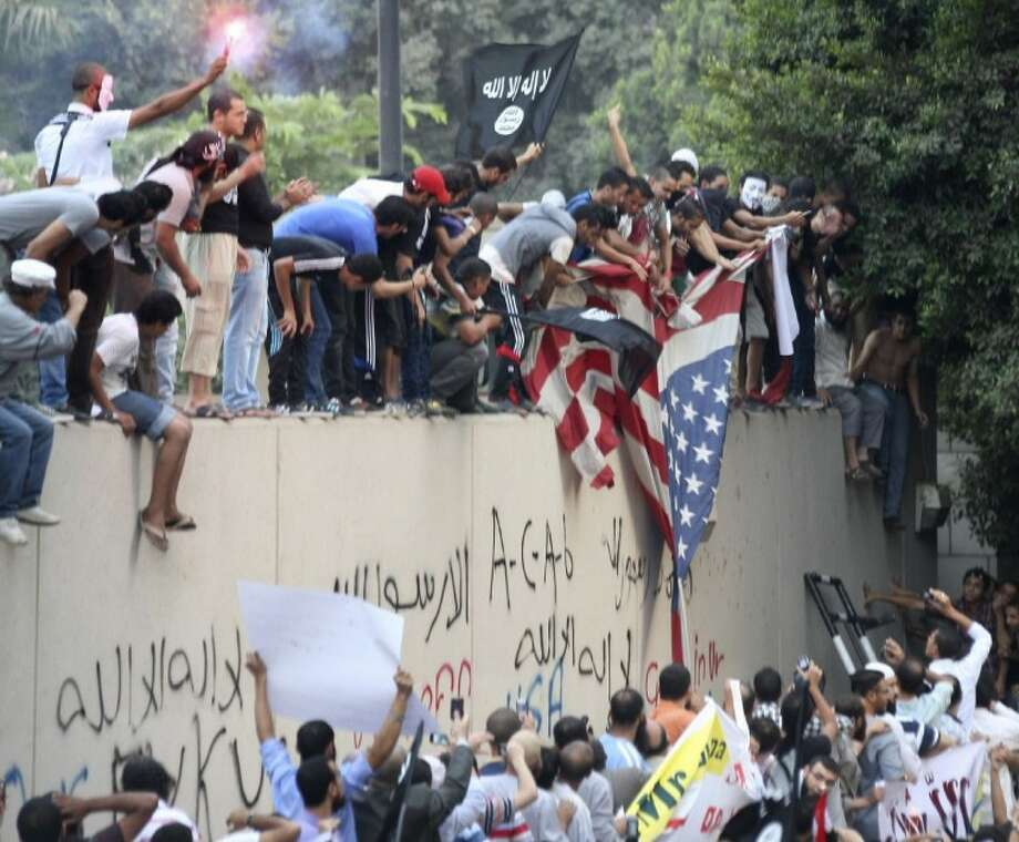 Protesters destroy an American flag pulled down from the U.S. embassy in Cairo, Egypt on Tuesday, the 11th anniversary of the Sept. 11, 2001 terror attacks on the U.S. Egyptian protesters, largely ultra conservative Islamists, climbed the walls of the U.S. embassy in Cairo, went into the courtyard and brought down the flag, replacing it with a black flag with Islamic inscription, in protest of a film deemed offensive of Islam. Photo: Mohammed Abu Zaid