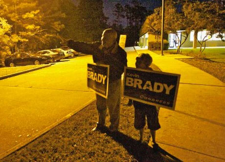 U.S. Rep. Kevin Brady, R-The Woodlands, performs some last-minute campaigning Tuesday with his son Sean, 10, outside Collins Intermediate School in The Woodlands as polling locations neared closing time. Photo: Staff Photo By Eric Swist