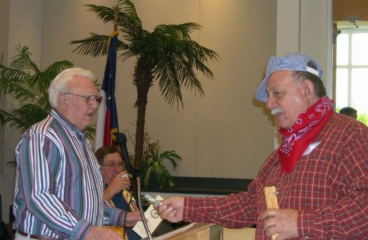 """Conroe Noon Lions Club member Eddie Risha, right, and the Lions District 2-S2 Tail Twister works out a """"fine"""" agreement with Past District Governor George Conner at past Lions District Mid-Winter Conference to be held this year in Houston."""