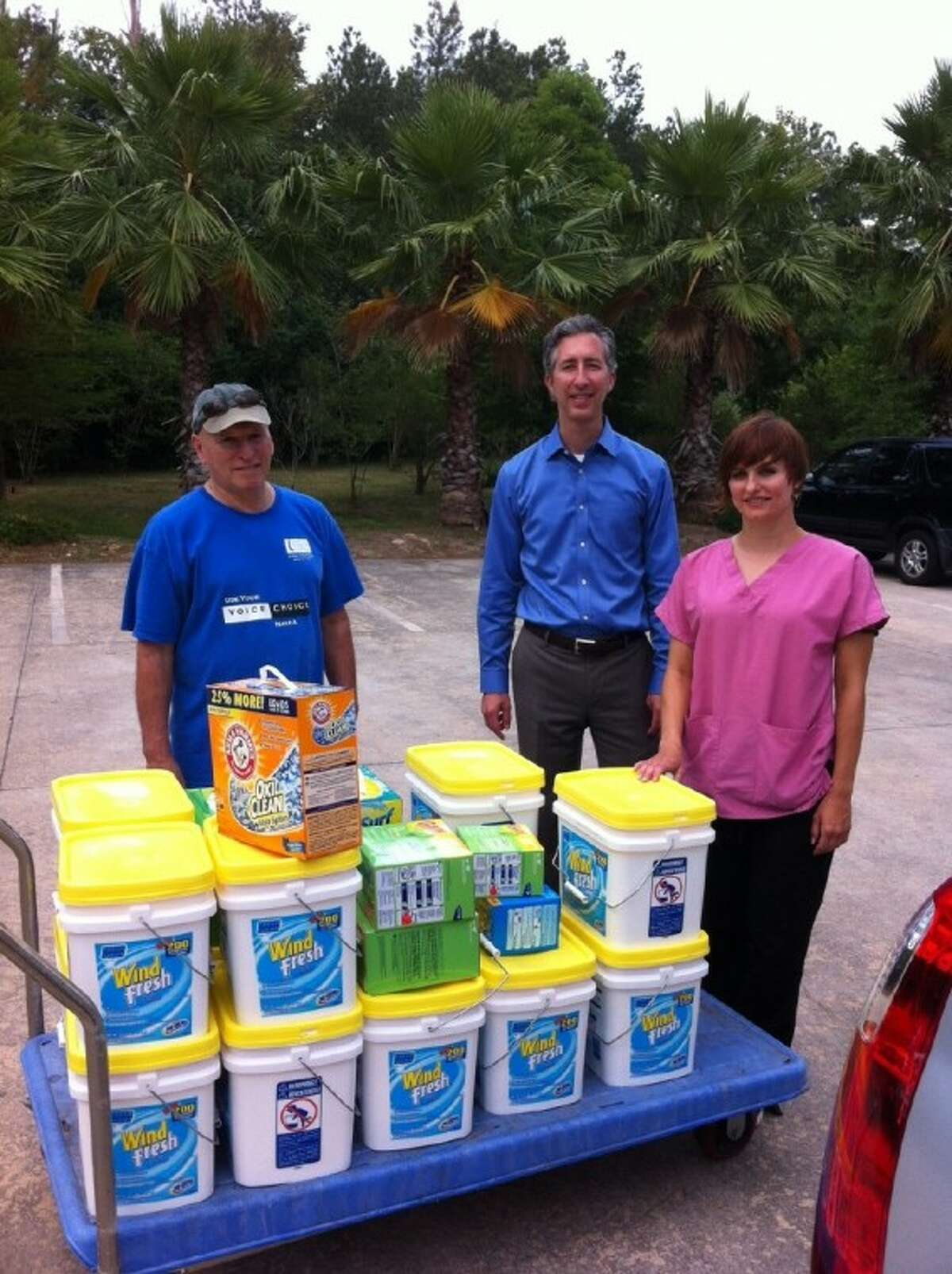 Woodlands Rotarian Todd Bryant, center, delivers laundry soap to volunteers at the Montgomery County Women's Shelter. The club provided the center with enough detergent to wash almost 3,500 loads of clothes.