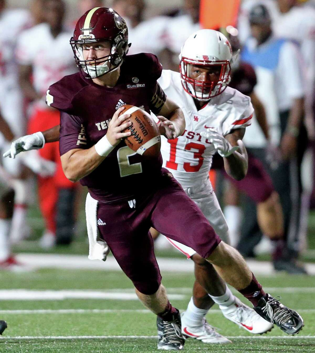 Texas State Bobcats quarterback Tyler Jones looks for running room under pressure from Houston Cougars cornerback Joeal Williams during second half action Saturday Sept. 24, 2016 at Bobcat Stadium in San Marcos, Tx. The Houston Cougars won 64-3.